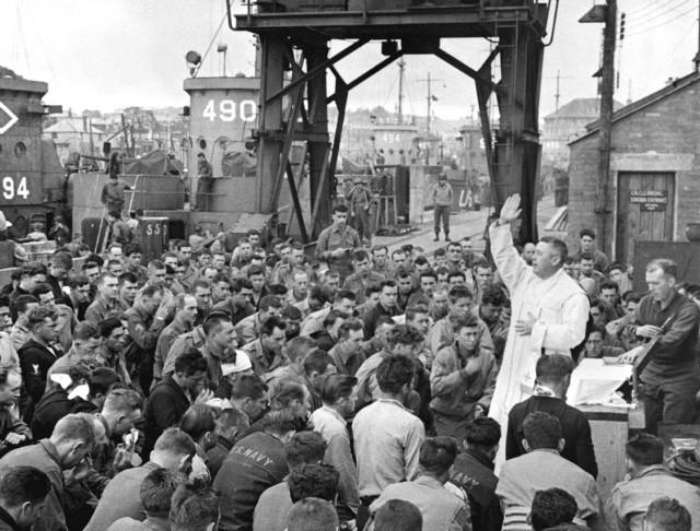 L'abbé Edward J. Waters donne la bénédiction finale de la sainte messe aux soldats qui vont débarquer en Normandie avec la première vague d'assaut